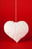 Corazón blanco hecho de lanas en un fondo rojo. Fotos de archivo libres de regalías