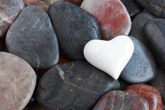 Corazón blanco rodeado por las piedras Imagenes de archivo