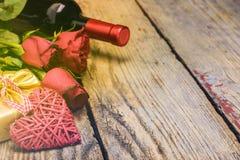 Corazón, caja de regalo, rosa roja y botella de vino Rose roja fotografía de archivo libre de regalías