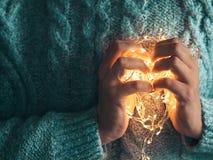 Corazón caliente, concepto del amor Las manos de las mujeres que sostienen una guirnalda Muchacha en un suéter azul con las luces imagen de archivo libre de regalías