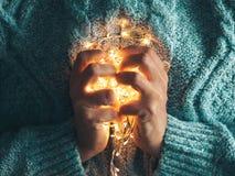 Corazón caliente, concepto del amor Las manos de las mujeres que sostienen una guirnalda Muchacha en un suéter azul con las luces foto de archivo