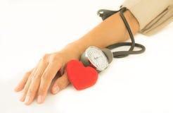 Corazón con el brazo de la mujer que comprueba la presión arterial fotos de archivo libres de regalías