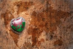 Corazón con la bandera nacional de País de Gales en un fondo del papel de la grieta del mapa del mundo del vintage ilustración del vector