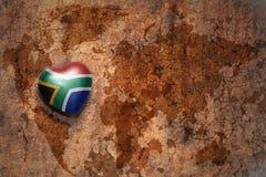 Corazón con la bandera nacional de Suráfrica en un fondo del papel de la grieta del mapa del mundo del vintage Imagen de archivo libre de regalías