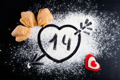 14 Corazón con la flecha en la harina en la tabla negra Galletas Imágenes de archivo libres de regalías