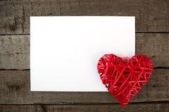 Corazón con la hoja de papel en un tablero de madera fotos de archivo libres de regalías