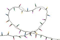 Corazón con las luces de la Navidad en el fondo blanco Imagen de archivo