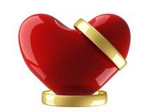 Corazón con los anillos de bodas en un fondo blanco. Fotografía de archivo