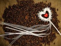 Corazón con los granos de café en la harpillera Imagenes de archivo