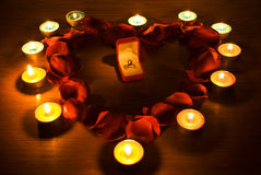Corazón con los pétalos y las luces de la vela Fotos de archivo libres de regalías