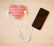 Corazón con smartphone y los auriculares Fotos de archivo