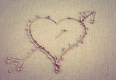 Corazón con una flecha dibujada en la arena imagenes de archivo