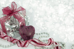 Corazón de color rojo oscuro con el regalo, la cinta, y las gotas de plata. Imagen de archivo