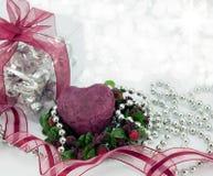 Corazón de color rojo oscuro con el regalo, la cinta, y las gotas de plata. Foto de archivo