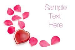 Corazón de cristal con los pétalos color de rosa Imágenes de archivo libres de regalías