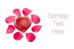Corazón de cristal con los pétalos color de rosa Foto de archivo