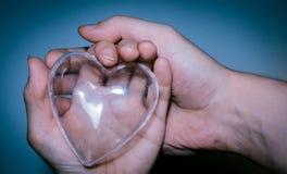 Corazón de cristal en el ` s de las mujeres y mano del ` s de los hombres en fondo azul imagen de archivo