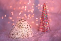 Coraz?n de cristal en una nieve y fondo rosado borroso entonado del bokeh que brilla con las luces que brillan intensamente Decor fotos de archivo