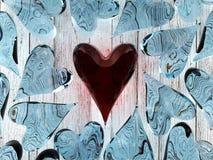Corazón de cristal rojo entre corazones de cristal azules Fotografía de archivo