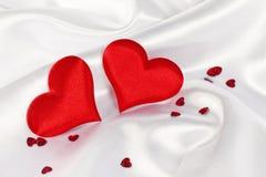 Corazón de dos rojos en la seda blanca fotos de archivo libres de regalías