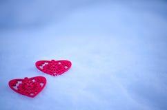 Corazón de dos rojos en una tarde de la nieve imagenes de archivo