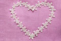Corazón de encaje romántico en fondo rosado Imagen de archivo