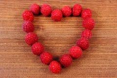 Corazón de frambuesas frescas en la tabla de madera, símbolo del amor Imagenes de archivo