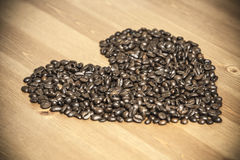 Corazón de habas del coffe en la tabla Fotos de archivo