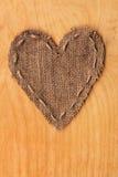 Corazón de la arpillera, mentiras en un fondo de la madera Fotografía de archivo libre de regalías