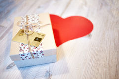 Corazón de la caja y del papel de regalo en la tabla de madera Foto de archivo libre de regalías