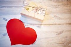 Corazón de la caja y del papel de regalo en la tabla de madera Imágenes de archivo libres de regalías
