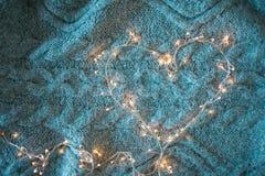 Corazón de la guirnalda con las luces que brillan intensamente en el fondo de una manta gris mullida fotografía de archivo libre de regalías