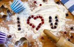 Corazón de la harina, del rodillo, de bayas y de utensilios para cocer en fondo de madera Día feliz del `s de la tarjeta del día  Imagen de archivo libre de regalías