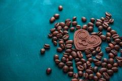 Corazón de la mentira oscura del chocolate entre los granos de café en un backgro oscuro imagen de archivo