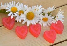 Corazón de la mermelada con una guirnalda de margaritas en los tableros de madera Imágenes de archivo libres de regalías