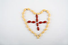 Corazón de la píldora con la cruz Fotos de archivo libres de regalías