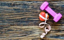 corazón de la pesa de gimnasia, de la cinta métrica y del rojo en el fondo de madera, S Foto de archivo
