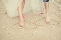 Corazón de la pintura de las piernas de los pares en la arena Foto de archivo libre de regalías