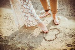 Corazón de la pintura de las piernas de los pares en la arena fotos de archivo libres de regalías