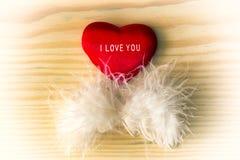 Corazón de la tarjeta del día de San Valentín con la pluma blanca en una madera ligera Foto de archivo libre de regalías