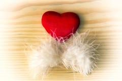 Corazón de la tarjeta del día de San Valentín con la pluma blanca en una madera ligera Imagenes de archivo