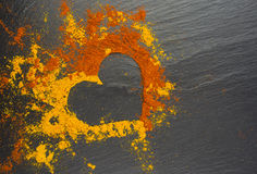 Corazón de la tarjeta del día de San Valentín de las especias curry y paprika en el fondo negro 14 de febrero foto de archivo