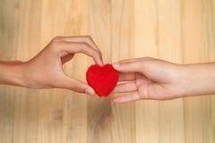 Corazón de la tarjeta del día de San Valentín en las manos masculinas y femeninas El donante femenino de la mano oye Fotos de archivo