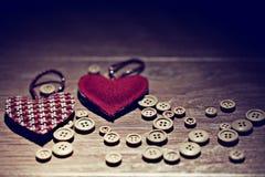 Corazón de la tarjeta del día de San Valentín entre los botones Fotografía de archivo