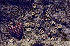 Corazón de la tarjeta del día de San Valentín entre los botones Imagenes de archivo