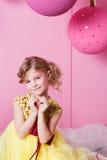 Corazón de la tarjeta del día de San Valentín para hacer sus fingeres Niño bonito de la muchacha 6 años en un vestido amarillo Be Fotos de archivo