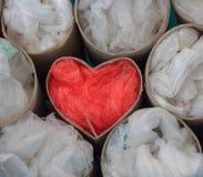 Corazón de las bolsas de plástico y de los tubos de la cartulina Imagen de archivo libre de regalías