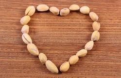 Corazón de las nueces de pistacho en la tabla de madera, consumición sana fotografía de archivo libre de regalías