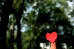 Corazón de las tarjetas del día de San Valentín en finger Imagen de archivo libre de regalías