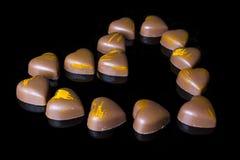 Corazón de los chocolates con leche del lado en negro Foto de archivo libre de regalías